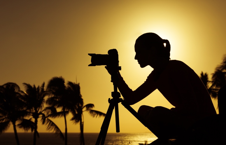 Female photographer taking pictures of the sunset.